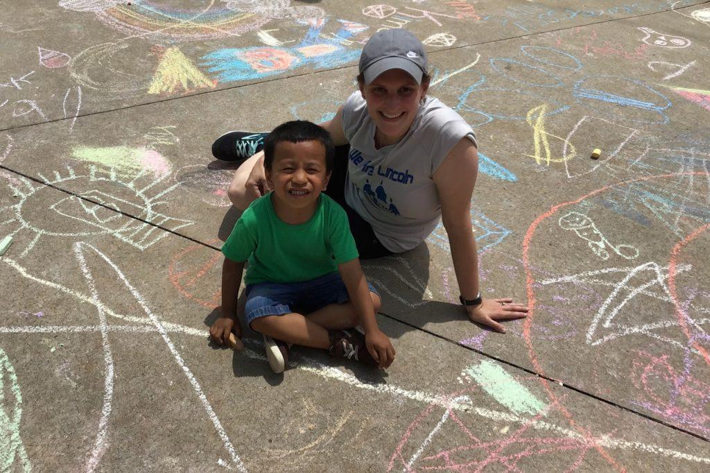 Art teacher with student on sidewalk with chalk.