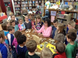 Mrs. Dalton shows her rock collection to first grade students.